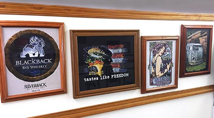 Wall of framed custom shirt art